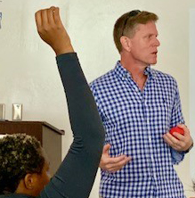 Photo shows John Giggie speaking before the class and a student raising their hand with a question.