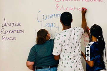 Image of Central High Students writing on a white board.