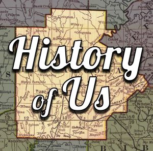 """History of Us Logo, which is a map of Tuscaloosa County with the words """"history of us"""" imposed above."""
